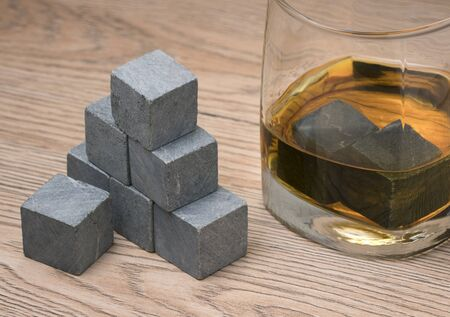 Glass with whiskey and whiskey stones on wooden background Imagens