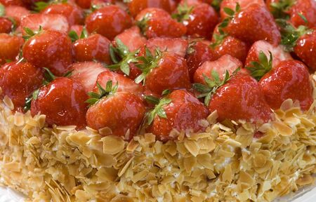 Fresh fruit cake with strawberries and sliced nuts. Close up view. Banco de Imagens