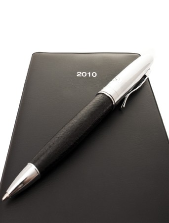 black notebook and a pen isolated on white - your plans for 2010  photo