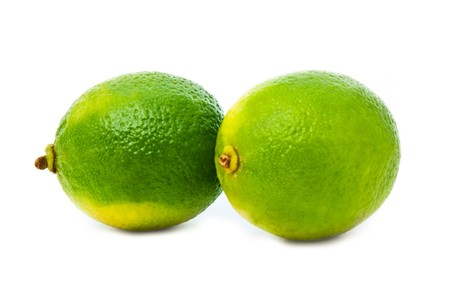 two green fresh limes isolated over white photo