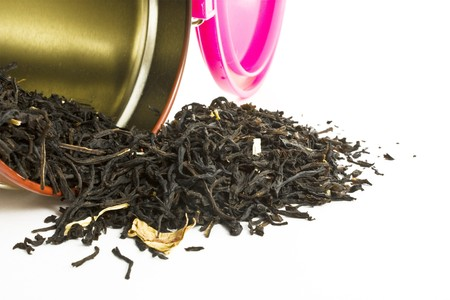 scattered tea in a tin isolated on white photo