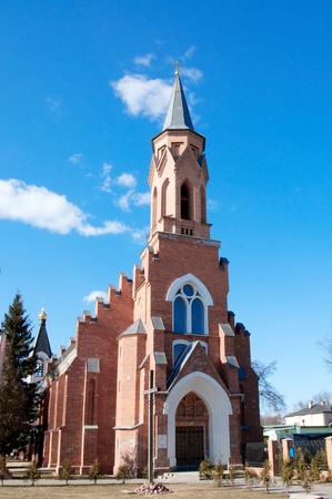 red brick catholic cathedral over blue sky photo