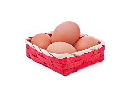 eggs in a wicker red basket on white background Stock Photo - 9958272