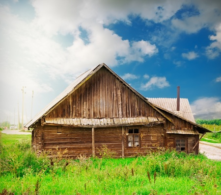 farm structures: vinatge wooden house in the countryside over blue sky with artistic lights and shadows added