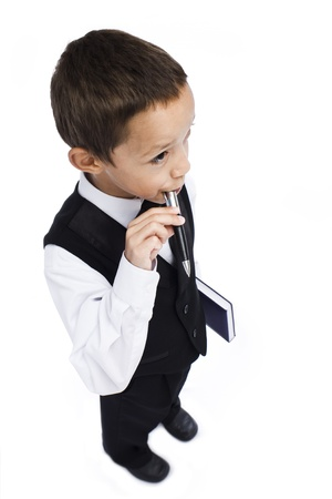 boy holding pen in his mouth holding book in his hand photo