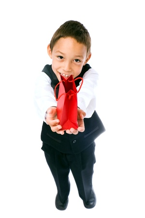 boy holding red bag with a gift in his hands isolated on white