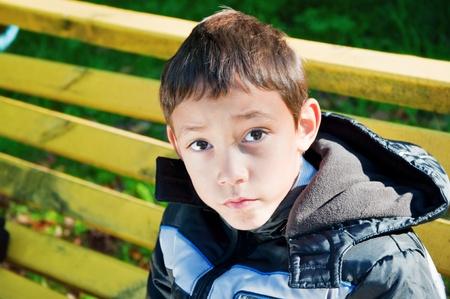 portrait of a sad boy sitting on a bench in a park photo