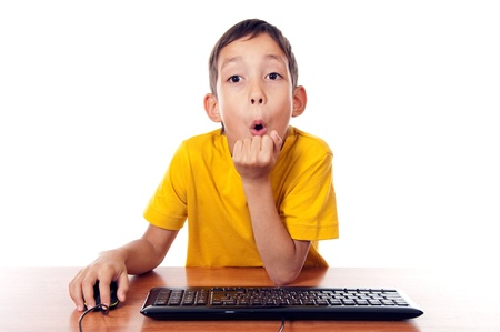 wondered: wondered boy sitting in front of computer with expression on his face isolated on white Stock Photo