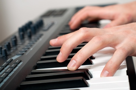 keyboard player: closeup shot of male hands playing the piano in the studio  Stock Photo