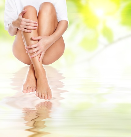 massaged: female legs being massaged under clean water waves over green spring background - spa and healthcare concept