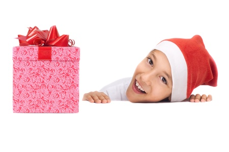 christmas paste: boy in christmas red hat holding a gift box with happy expression on his face with white copyspace to paste your advert or banner isolated on white background