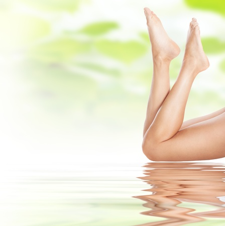 foot massage: healthy sexy slender female legs on water - spa and healthcare concept