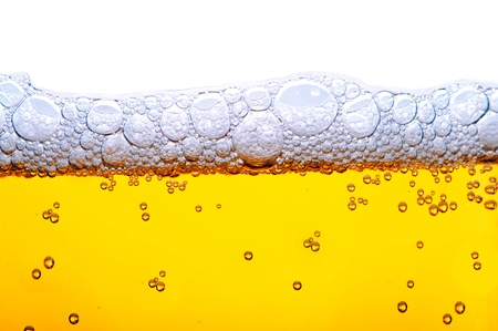buble: close up shot of yellow beer with foam and bubbles on white background