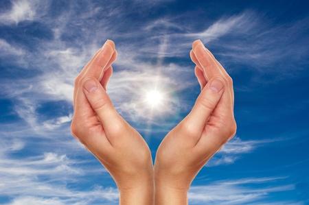 manos orando: manos femeninas sobre el cielo azul con nubes para el concepto de la religión y la protección del medio ambiente