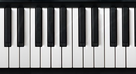 electronic piano keyboard closeup with black and white piano keys