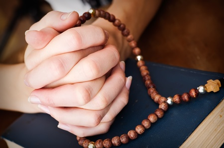 female hands with rosary and blue bible book  praying  on wooden table surface