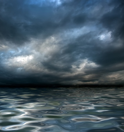 dark cloudy stormy sky with clouds and waves in the sea - global warming concept Stock Photo