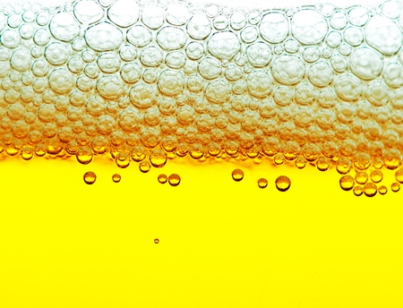 foam party: close up shot of yellow beer with foam and bubbles on white background