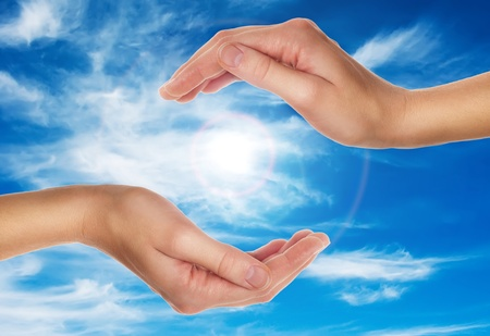 and harmony: female hands over blue sky with clouds - religion and environment protection concept