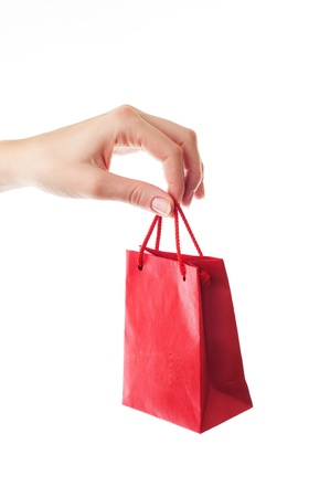 gift bags: female hand holding red gift bag with present with her fingers - shopping and holiday concept