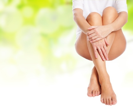 massaged: female legs being massaged over green spring background with white copyspace to place your advertisement- spa and healthcare concept  Stock Photo