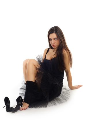 female ballet dancer in black dress with beautiful healthy brown long hair sitting on white background near her shoes photo