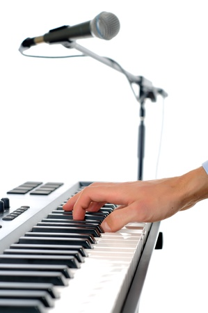 maicrophone and male hands playing the piano in the studio isolated on white - shallow pepth of firld with focus plased on hand photo