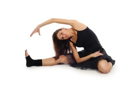 female ballet dancer in black dress doing exercises on white background  photo