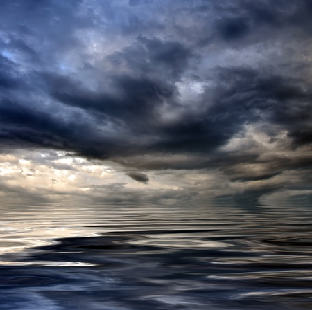 dark cloudy stormy sky with clouds and waves in the sea - global warming concept  photo