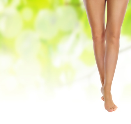 healthy sexy slender female legs over green natural spring background - spa and healthcare concept  photo