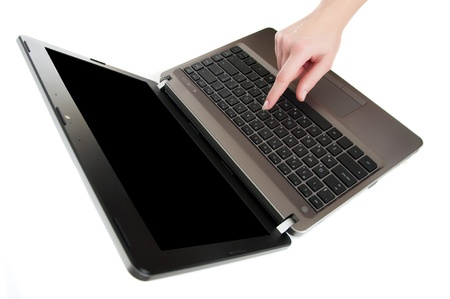 female hand pushing a button on laptop keyboard with the finger with black copy-space to place advert photo