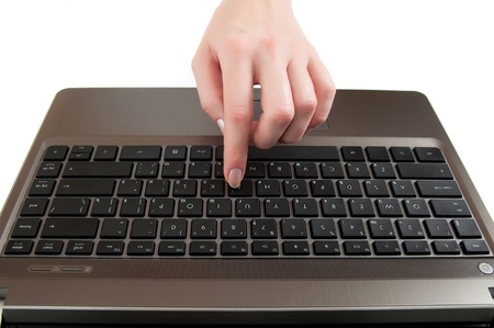 female hand pushing a button on laptop keyboard with the finger  photo