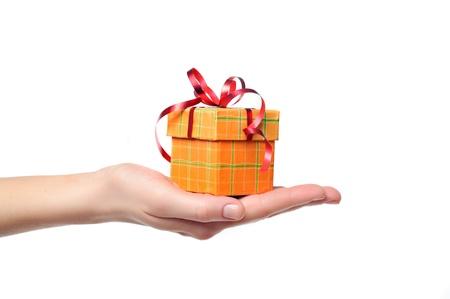 Weibliche Hand rot und gelb Geschenkbox mit einem Bogen auf weißem Hintergrund