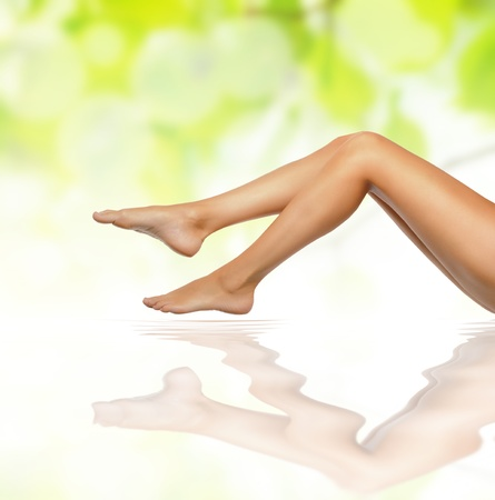 healthy sexy slender female legs over green natural spring background - spa and healthcare concept  Stock Photo