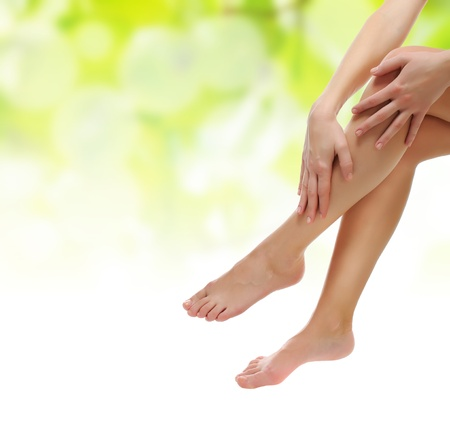 healthy sexy slender female legs being massaged over green natural spring background - spa and healthcare concept  photo