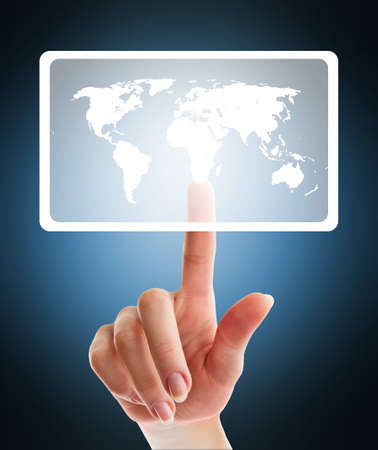 female hand pushing virtual button with world map on touch screen interface over blue backgrount - education and science concept photo