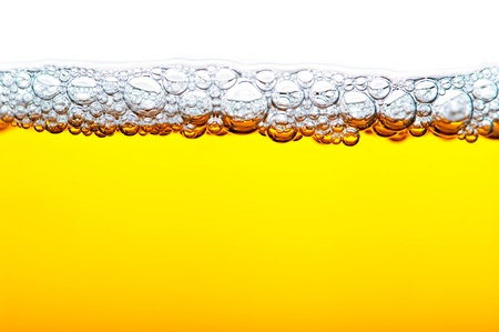 close up shot of yellow beer with foam and bubbles  on white background photo