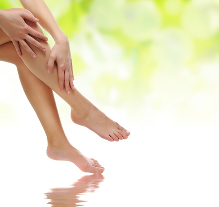 massaged: healthy sexy slender female legs being massaged over green natural spring background - spa and healthcare concept
