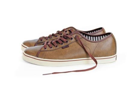 untied: dos desat� zapatillas de deporte de cuero marr�n aisladas sobre fondo blanco Foto de archivo
