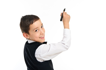 portrait of a young school boy wrighting or drawing something with black point pen isolated on white background photo