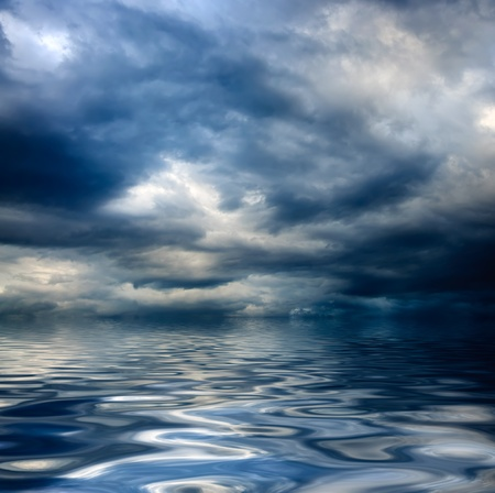 grey water: dark cloudy stormy sky with clouds and waves in the sea - global warming concept