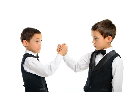 two brothers twins playing arm wrestling isolated on white background photo