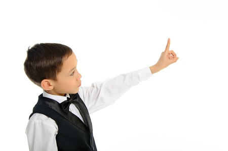 Portrait of a young school boy in black suit touching something with his finger isolated on white photo