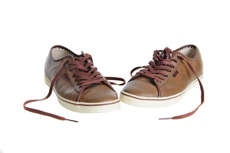 two untied brown leather sneakers isolated on white background photo