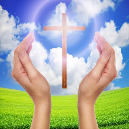 jesus hands: female hands praying with a wooden cross in cloudy sky under green field of grass - easter concept