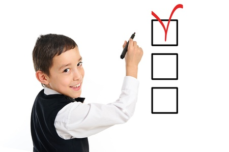 kids writing: portrait of a young school boy wrighting or drawing checkboxes with black point pen isolated on white background