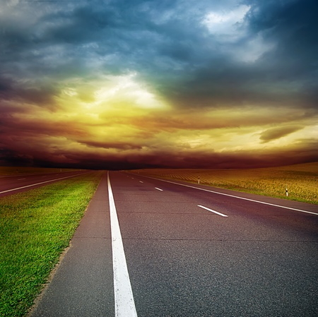 asphalt road in the field over stormy dark cloudy sky - sunset in the evening  photo