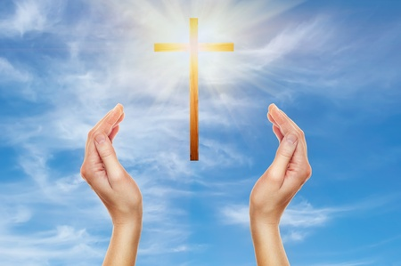 christian trust: female hands praying with a wooden cross in cloudy sky - easter concept