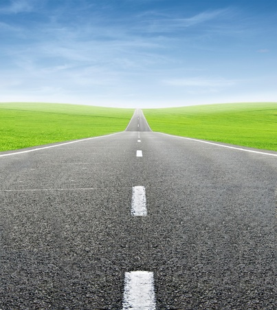 moving forward: green field and road over blue sky - travel and tranportation concept Stock Photo
