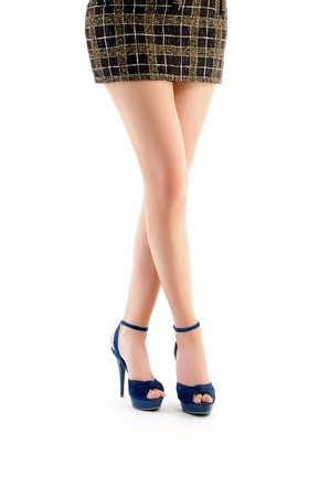 female legs in blue shoes and brown skirt isolated on white background
